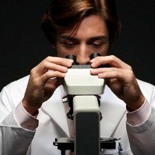 Man Looking in Microscope --- Image by © Sean Justice/Corbis