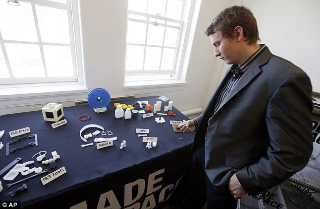 Aaron Kemmer, CEO and co-founder of Made in Space, looks through some items made with the company's 3D printer