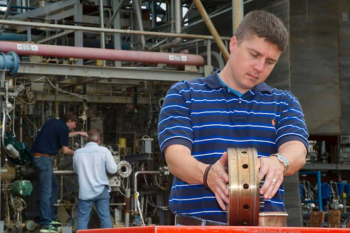 A 3D-printed rocket injector is inspected before being attached.