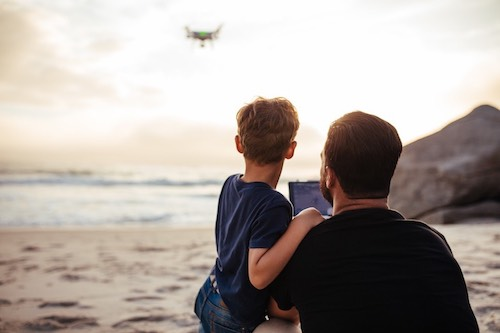 Father and son flying drone at the beach